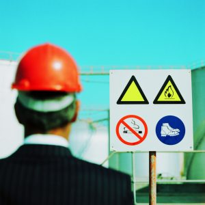 Businessman Wearing a Hard-Hat Looking at a Hazard Sign